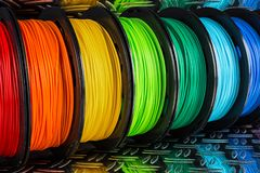 Colorful bright row of spool 3d printer filament black metal background royalty free stock images