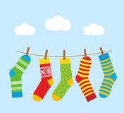 Colorful bright socks on a rope with clothespins against a background of sky and clouds. Stock Image