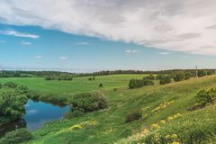 Colorful Bright Sunny Green Field Landscape With Blue Cloudy Sky, River Trees And Hills royalty free stock photography