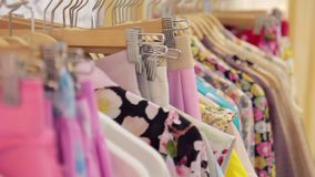 Colorful bright women`s clothing on a hanger in the store. Hanger with trendy clothes in store stock video footage