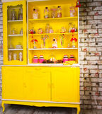 Colorful bright yellow welsh dresser. With its shelves filled with decorative glass jars of kitchen ingredients and decorated with striped candy canes and Royalty Free Stock Image