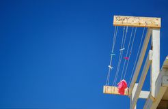 Colorful brightly clothespins and pink rag hanging on rope at the rescue station on background of blue sky Stock Images