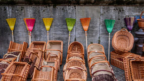 Colorful brooms stacked against a wall Royalty Free Stock Photos