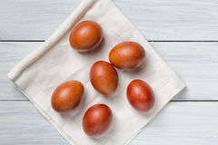Colorful brown easter eggs on cloth and white wooden table Royalty Free Stock Images