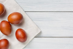 Colorful brown easter eggs on cloth and white wooden table with free space. Focus on eggs Stock Photography
