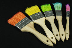 Colorful brushes arranged in an arc. On an isolated black background Royalty Free Stock Images