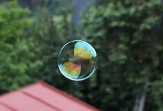 A colorful bubble created by bubble blower. In beautiful circle flying in the air and on the background there are trees and roof royalty free stock photography