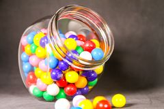 Colorful Bubble Gum Balls in  Glass Cannister Black Background. Lot`s of Small Colorful Bubble Gum Balls Spilling from a Clear Glass Cannister.  with a Black Royalty Free Stock Images