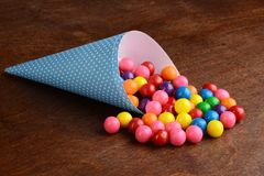 Colorful bubble gumballs in a blue paper cone. On wood table royalty free stock photo
