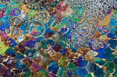 Colorful Bubbles. Bubbles on water that is flowing over colored tiles stock image