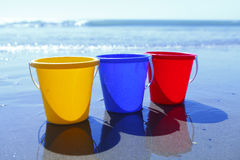 Colorful buckets on beach Royalty Free Stock Photos
