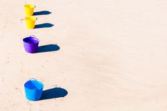 Colorful buckets on the beach sand Stock Photography
