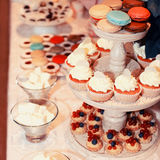 Colorful buffet table with macaroons and cakes Stock Images