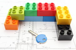 Colorful building blocks and key on housing plan. Colorful building blocks and key lying on construction drawing of house Stock Photography