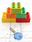 Colorful building blocks and key on housing plan. Colorful building blocks and key lying on construction drawing of house Stock Image