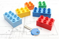 Colorful building blocks and key on housing plan. Colorful building blocks and key lying on construction drawing of house Royalty Free Stock Photography