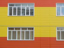 Colorful building facade with window and yellow and orange siding, a background pattern abstract.  Royalty Free Stock Photos