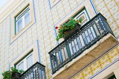 Colorful building with a green balcony decorated with flowers in Lisbon. Portugal stock photography