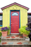 Colorful Building with Red Door. A quaint, green building with a red door, blue door jam and pink trim. Plants and creative brick steps are in front of the door stock photo