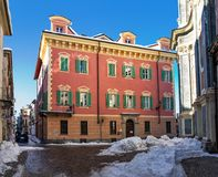 Colorful building on snowy street in Cuneo. Typical colorful building on narrown cobblestone street with snow in city of Cuneo in Piedmont, Northern Italy Stock Photo