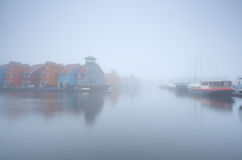 Colorful building on water and boats in fog Royalty Free Stock Photo