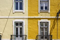 Colorful building with windows. Bright yellow facade with square symmetrical windows in Lisbon, Portugal royalty free stock photos