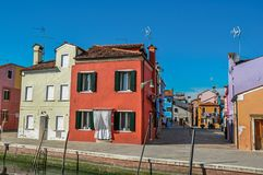 Colorful buildings with clothes hanging in canal of Burano. Overview of colorful buildings and clothes hanging in a blue sunny day, in front of a canal at Burano royalty free stock photos
