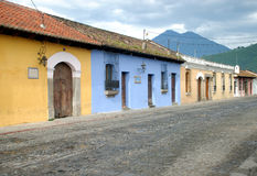 Colorful buildings cobble stone streets. Antigua Guatemala in Central America. Early morning cobble stone streets, and colorful houses Royalty Free Stock Image