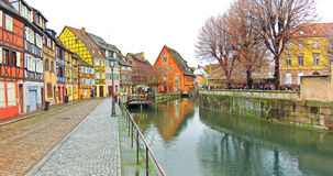 Colorful buildings in front of a river in Colmar, France. Stock Images