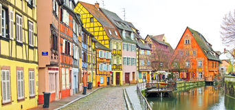 Colorful buildings in front of a river in Colmar, France. Stock Photos
