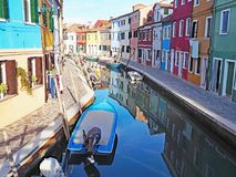 Colorful buildings reflect in the canal on the island of Burano in Italy. Colorful buildings reflect in the canal on the island of Burano in Venice, Italy royalty free stock images