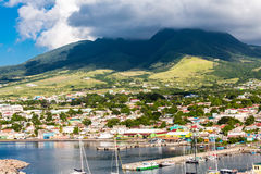 Colorful Buildings up Green Hills on St Kitts Stock Image