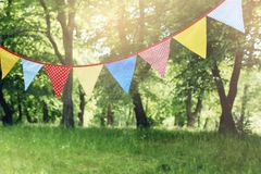 Colorful bunting flags hanging in park. Summer garden party. Outdoor birthday, wedding decoration. Midsummer, festa