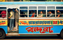 Colorful bus driving on indian street and many different people inside of it Royalty Free Stock Image