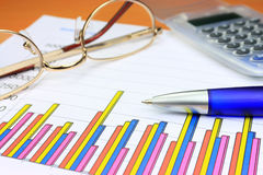 Colorful business chart. Blue pen calculator and eyeglasses Royalty Free Stock Photos