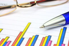 Colorful business chart. Blue pen and eyeglasses (shallow depth of field Royalty Free Stock Image