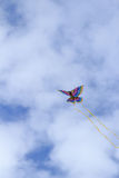 Colorful butterfly kite across a blue sky. A rainbow colored butterfly kite flies across a blue sky in summer royalty free stock photo
