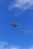 Colorful butterfly kite across a blue sky. A rainbow colored butterfly kite flies across a blue sky in summer stock photo