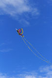 Colorful butterfly kite across a blue sky. A rainbow colored butterfly kite flies across a blue sky in summer royalty free stock images