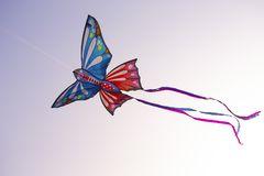 Colorful butterfly kite with bright ribbons is flying in the sky stock image