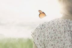 A colorful butterfly leans delicately on the shoulders of a girl. In the middle of nature royalty free stock photos