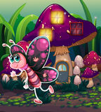 A colorful butterfly near the lighted mushroom house Stock Images