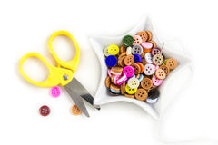 Colorful buttons and scissors on white background. Stock Photo