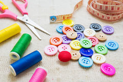 Colorful buttons, threads and scissors on fabric Royalty Free Stock Photos