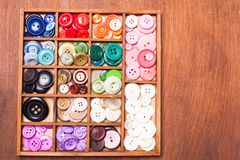Colorful buttons in box. Colorful buttons in a wooden box for design Royalty Free Stock Images