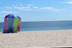 Colorful cabana. Brightly colored cloth cabana flowing in the wind on a sandy beach Royalty Free Stock Images
