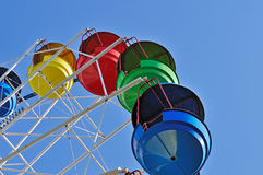 Colorful cabins of ferris wheel against the blue sky Stock Images