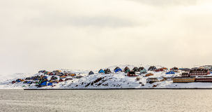 Colorful cabins on the hill covered in snow, Aasiaat city Stock Image