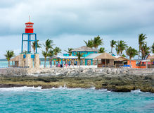 Colorful cabins, tower, palm trees and sand Royalty Free Stock Photography