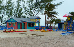 Colorful cabins, tower, palm trees and sand Stock Images